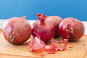 Four red onions on a cutting board with onion peels coming off