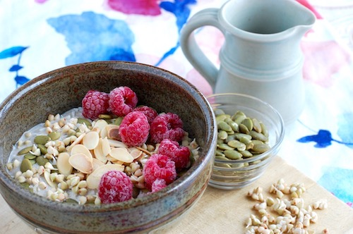 Sprouted buckwheat porridge served in a bowl, garnished with raspberries, toasted almonds, hemp hearts and pumpkin seeds.
