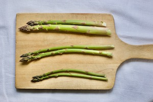 Asparagus on a cutting board separated into three sizes: thin, medium, thick