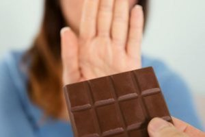 A women rejecting a chocolate bar to reduce high oxalate symptoms