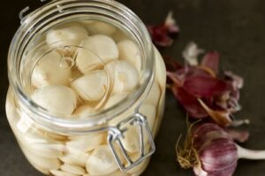 Peeled garlic in an airlock jar with a fermentation weight submerging the cloves